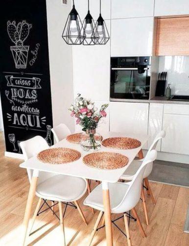 Cozinha aberta, mesa branca com cadeiras brancas e ao lado uma parede de lousa com desenhos em giz de cactos