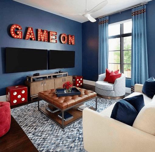 Uma sala decorada com paredes azuis, puff de couro marrom e em cima de duas tvs, letras com micro lâmpadas forma a farse em ingles , game on
