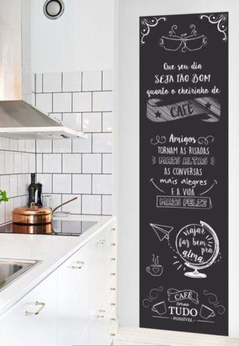 Cozinha com bancada branca e ao lado uma parede de lousa com escritos e desenhos tipo, café, que seu dia seja bom.