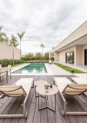 Aréa externa entre a casa e um muro tem uma piscina retangular, com deck de madeira e duas espreguiçadeiras