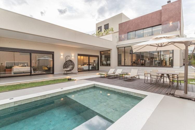 Casa grande em L e um lado com dois andares e na frente um deck de madeira e mesas e cadeiras, além de uma piscina retangular