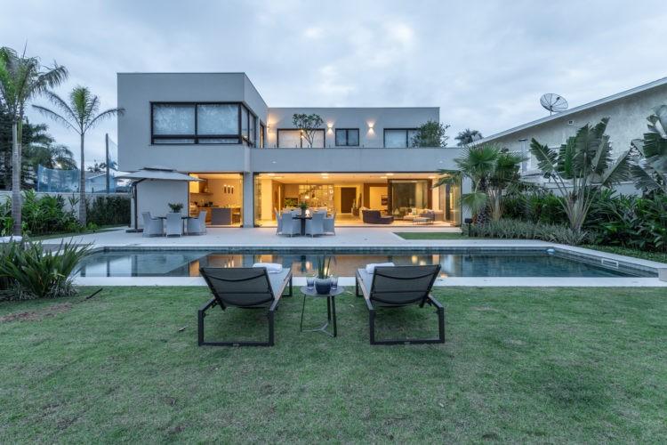Dicas e segredos para realizar o projeto da piscina dos sonhos. Fachada de uma casa com dois andares, com uma piscina na frete e epois um gramado com duas espreguiçadeiras