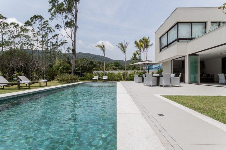 Casa com uma aréa externa bem grande e na fente uma piscina em formato retangular grande.