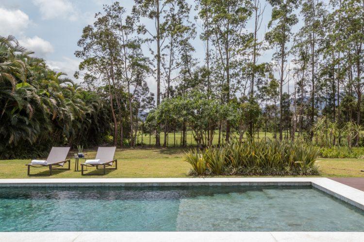 Um grande gramado com arvores e uma piscina