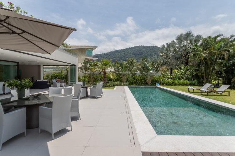Dicas e segredos para realizar o projeto da piscina dos sonhos, casa com aréa externa bem aberta e com uma piscina grande retangular, varanda com mesas e cadeiras