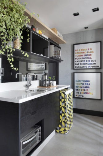 No trabalho, como se estivessem em casa, bancada branca, armários pretos e frigobar com adesivo estampado