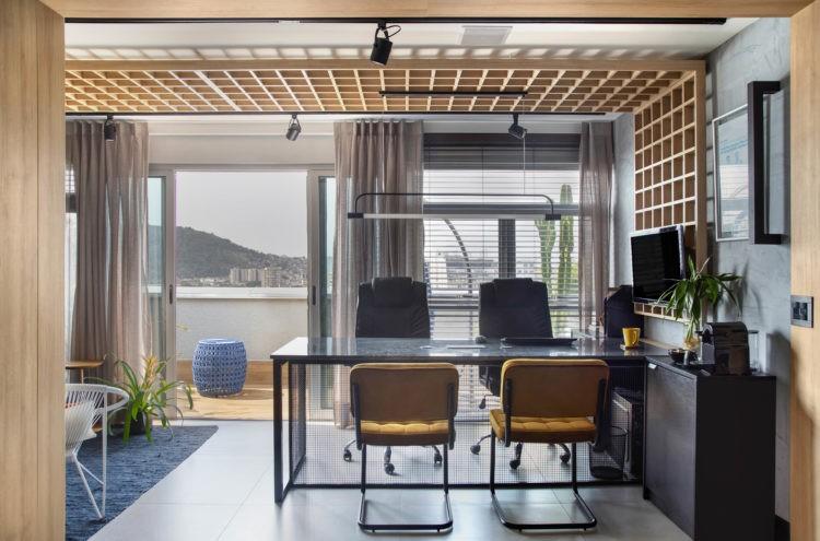 No trabalho, como se estivessem em casa, varanda do escritório com vista , e na frente, bancada de trabalho