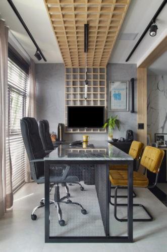 Bancada de escritório, com duas cadeiras pretas e em frente duas cadeiras amarelas. Painel em quadrados de madeira no teto descendo para a parede e uma tv