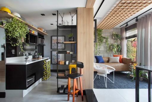 No trabalho, como se estivessem em casa, escritório nas cores cinza e amarelo, sofá em couro marrom, tapete azul e o teto com revestimento em quadrados de madeira