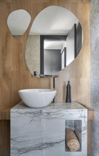Lavabo com parede revestida em madeira, dois espelhos em formatos orgânicos, bancada em mármore.