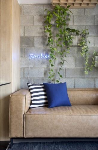 Parede de blocos de cimento, com alguns sobressaltados com plantas e um neon azul escrito sonhe