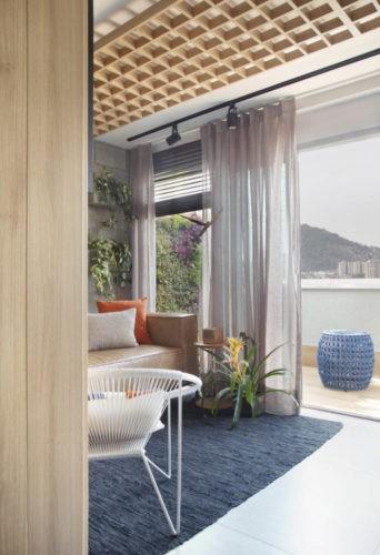 Sala do escritório, com sofá em couro marrom, tapete azul e cortina branca separando da varanda