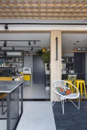 Escritório com clima de casa, teto com colmeias em madeira. trilho preto no teto, varanda e bancos amarelos