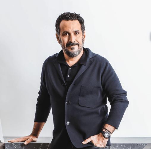 Foto do designer Pedro Franco, com barba e vestido de blusa e blazer preto