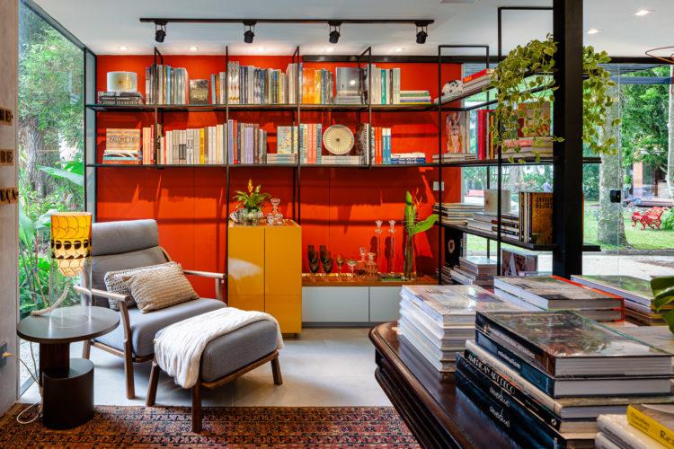 A loja e a livraria da CASACOR Rio. Um cantinho com uma estante de ferro vazada e cheia de livros , com a parede pintada de laranja. Em frete uma poltrona de leitura