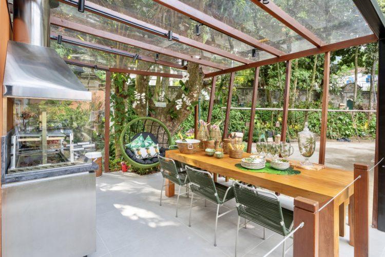 A loja e a livraria da CASACOR Rio, varanda gourmet da loja. Uma arvore no meio e uma balanço redondo, uma mesa em madeira.