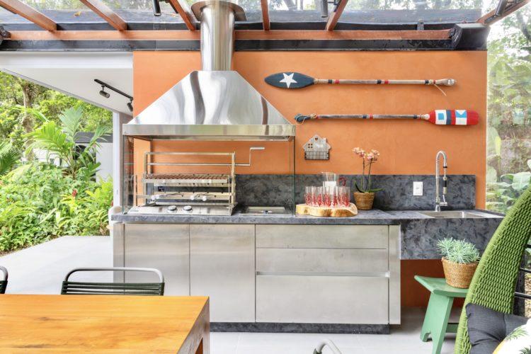 Uma parede pintada na cor laranja, na varanda com churrasqueira e remos enfeitando.
