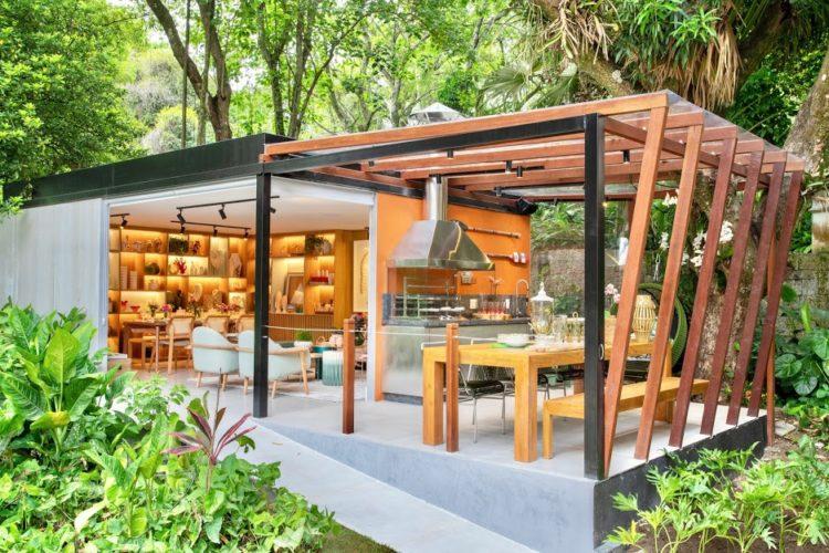 No meio do jardim, uma construção com sala e varanda com estrutura em ripas de madeira. Na mostra de decoração, Casa Cor