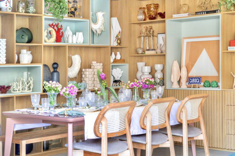 Um grande estante em madeira, repleta de nichos para expor os adornos, uma mesa de jantar posta e com arranjos de flores