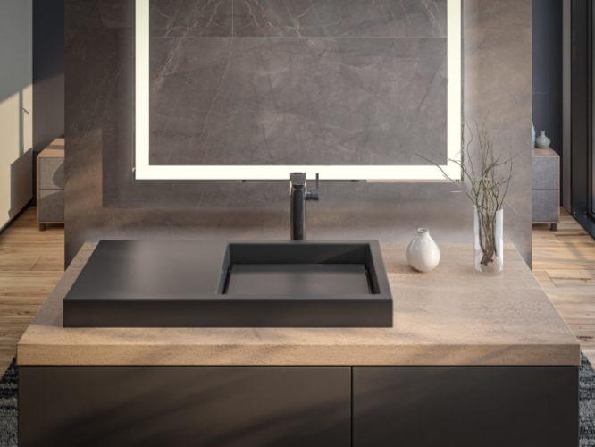 Bancada de banheiro com uma cuba preta retangular com metade coberta servindo de apoio