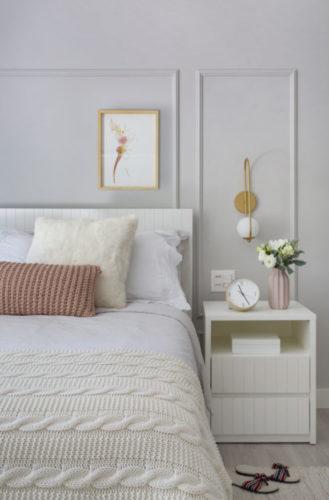 Quarto em tons claros, cama e colcha branca, parede com boiserie