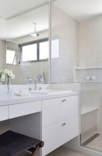 Banheiro em tons claros, bancada e armários brancos