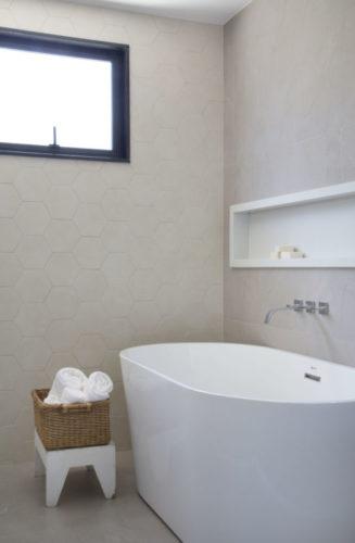 Banheiro claro, com uma banheira branca de piso perto da parede.