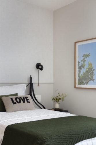 Quarto com paredes claras, roupa de cama branca com colcha verde escuro