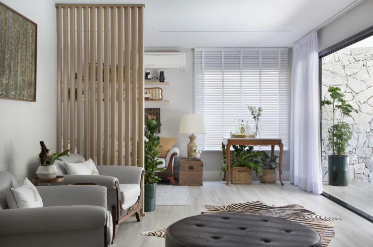 Ambiente integrado e claro, com uma grande abertura para a varanda. Tem duas poltronas cinza, um tapete de zebra e um puff redondo