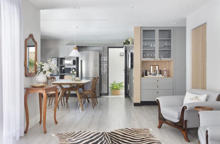 Cozinha integrada a sala de estar. Tapete de zenbra em frente a dias poltronas cinzas