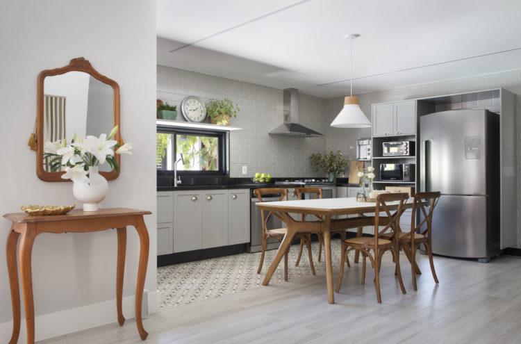Cozinha integrada a sala de estar, divisão no piso que tem de um lado réguas de madeira clara e no pedaço molhado, azulejo hidráulico bege