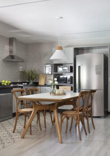 Cozinha aberta, mesa e cadeiras em madeira, Geladeira na cor aço inox e no piso, réguas de madeira clara e na parte molhada ladrilho hidráulico