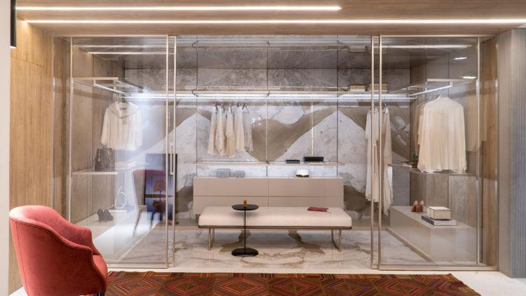 Closet entre paredes, com portas transparentes.
