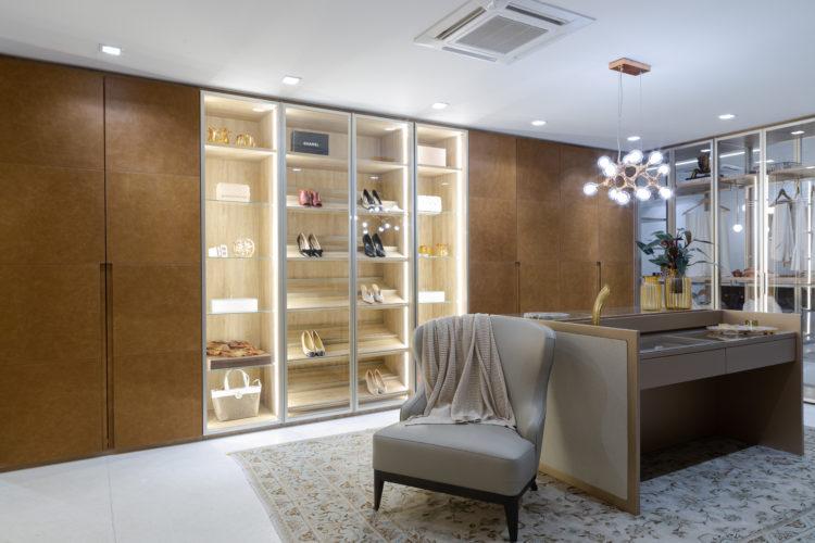Closet com portas em couro nas laterais, no centro, portas transparentes para visualizar bolsas e sapatos