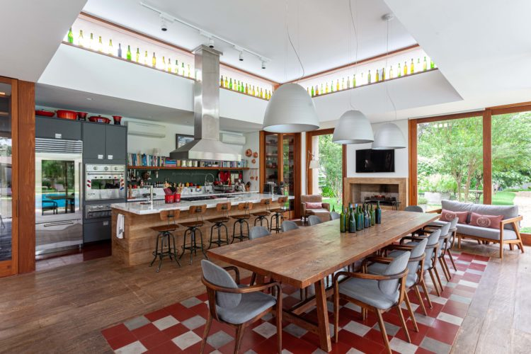 Complexo de lazer de uma família paulistana. Pavilhão grande com uma cozinha super equipada e mesa no centro para 12 pesssoas