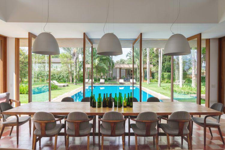 Vista da mesa de jantar para a piscina através de portas pivotantes