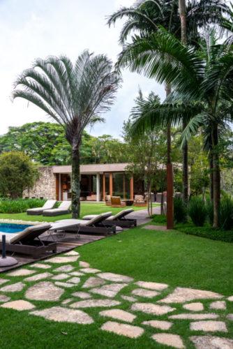Complexo de lazer de uma família paulistana. Um jardim com plameiras, uma casa em pedra ao fundo e espreguiçadeiras na piscina