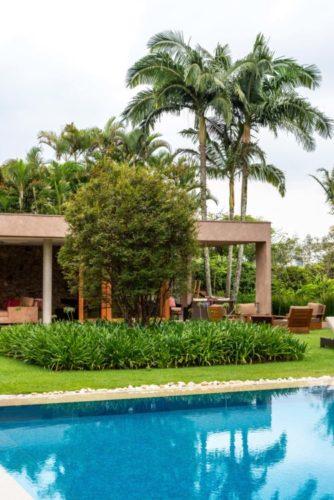 Uma casa com varanda aberta e um grande jardim em volta e uma piscina em frente.