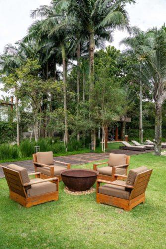 jardim com palmeiras, e no meio do gramado quatro cadeiras com uma lareira no centro