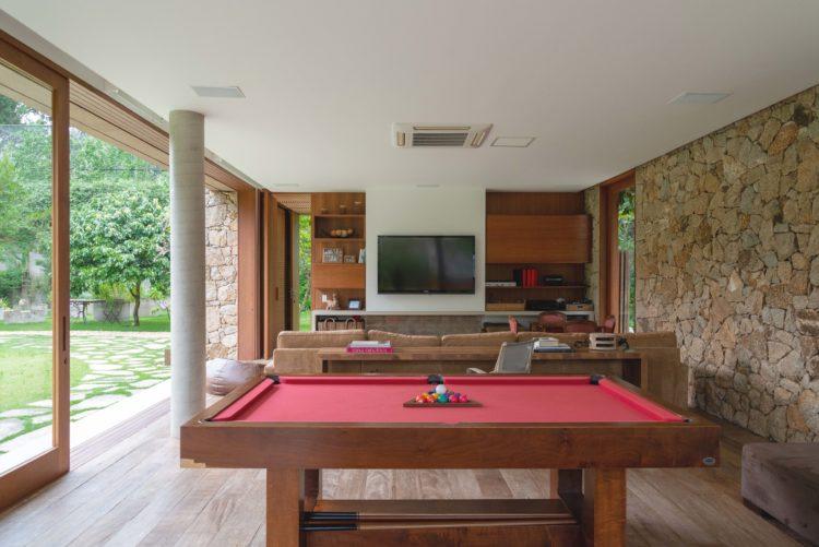Complexo de lazer de uma família paulistana, pavilhão a tv e de jogos. De um lado parede de pedra e em frente abertura total das esquadrias para o jardim
