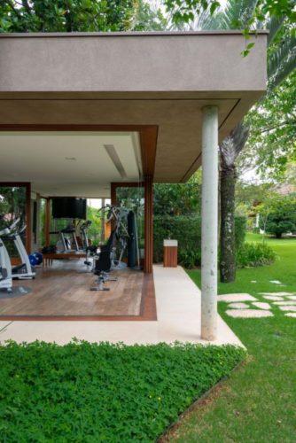 Anexo da casa principal para academia de ginastica, com abertura total das esquadrias para o jardim