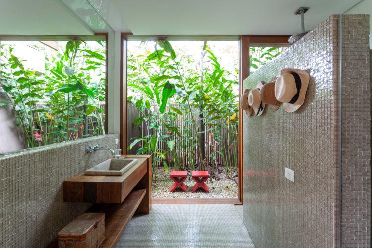 Banheiro com jardim aberto ao fundo com chuveiro ao ar livre