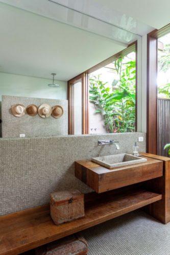 Banheiro com bancada e banco em madeira