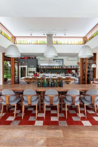 Piso em ladrilho hidráulico xadrez de vermelho e cinza embaixo da mesa de jantar e ao fundo uma cozinha super equipada