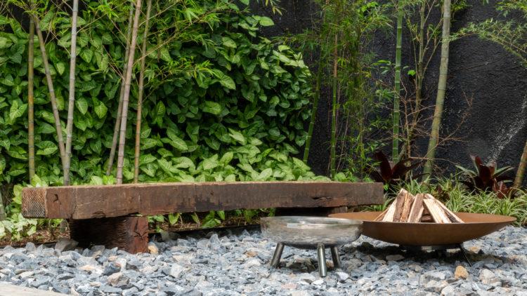 Jardim com um banco em madeira.