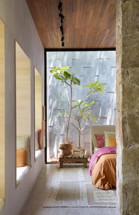 CASACOR RIO 2021 - Loft Contemporâneo. Teto revestido em madeira, parede e pedra separando o quarto do restante do loft