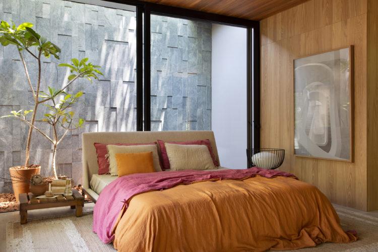 Cama encostada no vidro com esquadria e postas de correr, ao fundo parede de pedra
