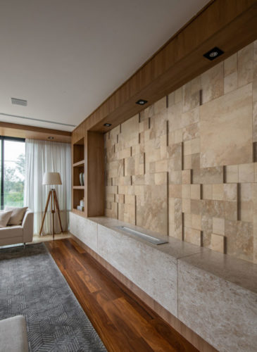 Com a temática Resgatar, Repensar e Ressignificar a Castelatto aposta em coleções inspiradas na Arquitetura Vernacular, na natureza, nas rochas clássicas e no design.. Porcelanato que imita mármore travertino  instalado em uma parede de uma sala de estar