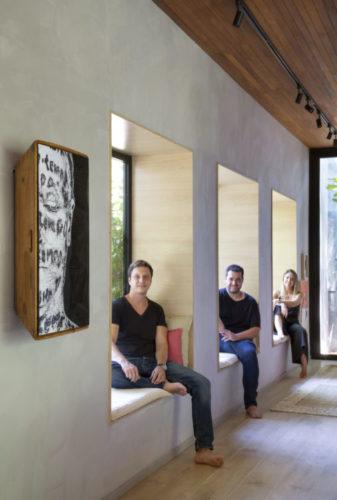 Foto do trio de arquitetos do escritório UP3 Arquitetura, cada um sentado e uma janela com banco