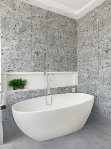 Paredes do banheiro revestida com porcelanato que imita pedra, uma banheira branca no meio.